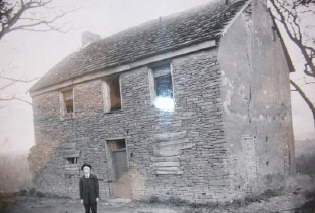 Colonel John Evans' Cabin in Morgantown, WV. Unknown Man in front of the cabin. (Ghost in window?) Photograph from the WV Regional Collection, Morgantown